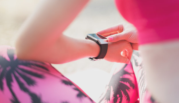 Close-up Shot. Female athlete using fitness app on her smart watch to monitor workout performance