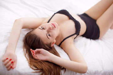 Sexy young woman model lying on bed