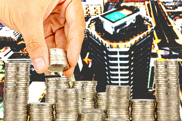 Exposure of Finance and Saving money banking concept,Hope of investor concept,Male hand putting money coin like stack growing business. background the city