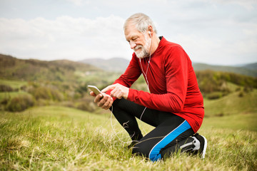 Active senior runner in nature with smart phone and earphones.