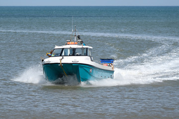 Shell fishing boat returning to shore with catch.
