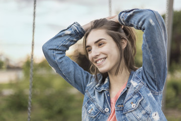 Smiling young woman with hand in hair looking away at park