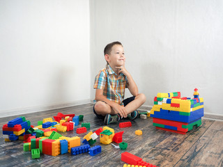 Happy boy is planning the construction of the house. Colorful details of a toy designer