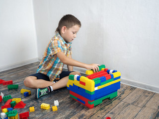 Boy builds multi-colored design. A lot of different parts
