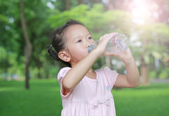 Close Up little girl drinking water from bottle in the park. Portrait outdoor.