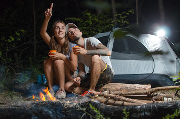 guy with the girl in the woods with a tent at night, sitting around the campfire