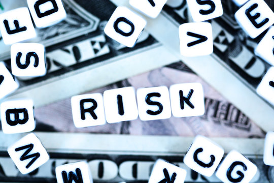 """Plastic letter beads spelling """"Risk"""" on us dollars background, financial or currency risk concept"""