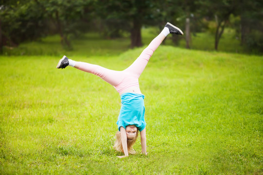 Active little school girl somersault outdoors