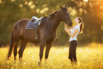 Young woman with her horse in evening sunset light
