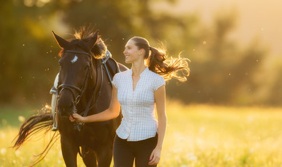 Young woman running with her horse in evening sunset light