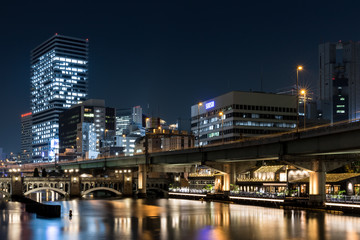 Modern office buildings and car bridge in Osaka at night illuminated with street lamps