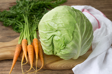 Fresh young cabbage and carrots with greens for coleslaw salad on a wooden board on a wooden table, selective focus. Healthy diet food