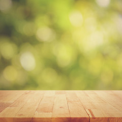 Vintage style wood table top on green bokeh background - can montage or display your products on top