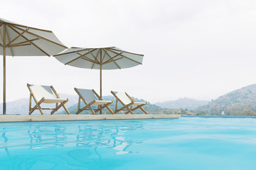Swimming pool, deck chairs, umbrellas, mountains