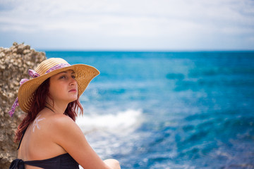 A young girl on a beach with a hat, sun and enjoys the sun, on the shoulder drawn sun from sun cream, summer, sun, sea