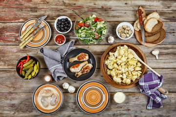 Dining table with fried potatoes in a frying pan, a salad of fresh vegetables, grilled chicken legs, seasoning sauces, bread. Concept: home food.