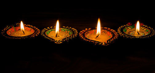 Four burning colorful candles indian style for Diwali celebration on black backgroun