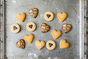Gebäck Kekse mit Schokolade in Herzform liegen dekorativ nach dem Backen auf Backblech