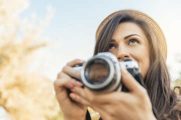 Young woman using a camera to take photo.