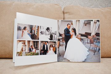 Pages of wedding photobook or wedding album on the sofa with cushions on the background. Wall mural