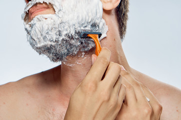 Man with a beard on a white isolated background shaves