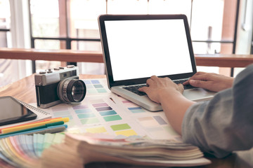 Color samples, color swatch samples, Draw architecture, Graphic designer selecting on colour chart, pens at workplace with work example in camera and laptop on wooden desk
