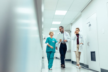 Group of medics discussing along hospital corridor Wall mural
