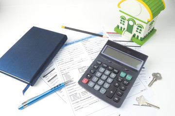 Mortgage application form, top view, house model, notebook, calculator, pen, pencil and key, business mortgage concept