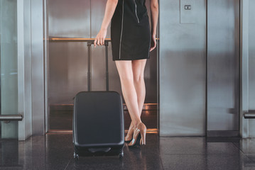 Charming girl is going in elevator with her luggage
