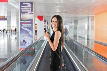 Cheerful elegant lady is holding suitcase and smartphone with smile