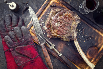 Barbecue Wagyu Tomahawk Steak as top view on burnt cutting board