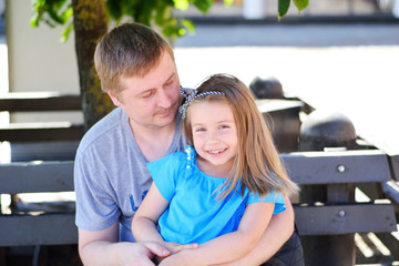 Father hugging daughter on the bench in the park on sunny summer day