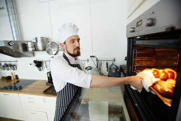 Professional baker taking out hot tray with crusty buns