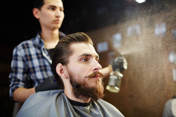 Young man having his hair styled in haircare salon