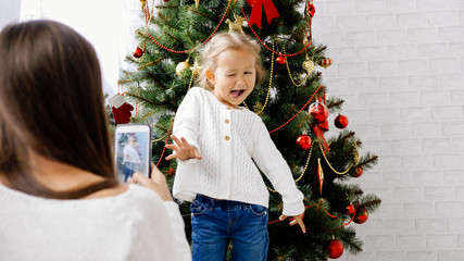 Mother making photo with smart phone of her little daughter near christmas tree