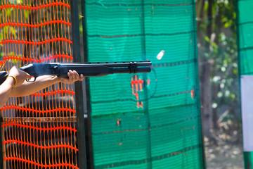 man shooting shotgun at shooting range