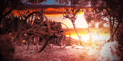 Old machinery in the farm land at sunset time. Empty copy space for Editor's text.