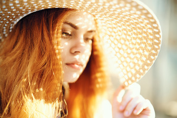 Young beautiful woman in a hat in the sun, light, summer
