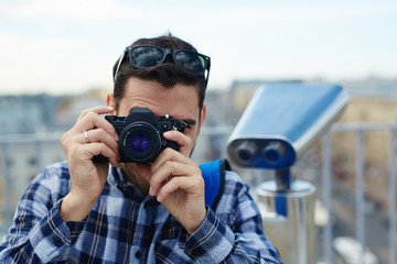 Portrait of young man standing on rooftop viewing platform against panoramic city view and coin-operated binoculars in background