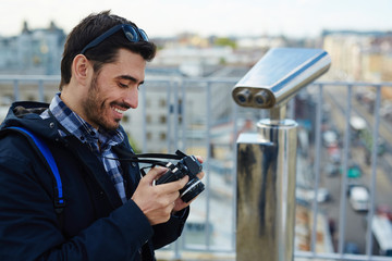 Side view portrait of modern solo tourist using photo camera to browse pictures while standing on rooftop