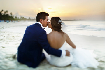 Groom kisses bride's forehead sitting on the beach