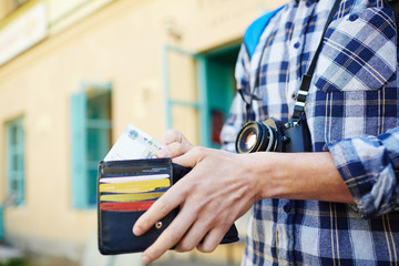 Closeup image of young tourist putting money in wallet, saving money  for vacation trips