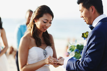 Bride puts a ring on groom's finger standing on the beach