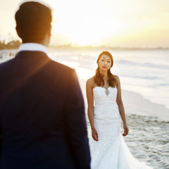 Look from behind groom's shoulder at stunning bride posing on the beach