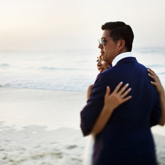 Bride and groom hug each other tender standing in the rays of golden sun on the beach