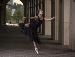 Young and incredibly beautiful ballerina is posing and dancing on the background of columns