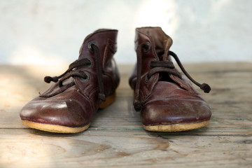 Old leather shoes on wooden flor; close up, selective focus.