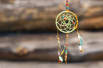 Dream catcher in the wind on a wooden background, selective focus