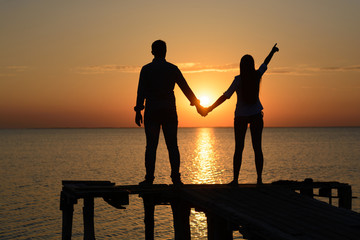 Silhouette of two young people (guy and girl) on a wooden bridge holding hands looking out to the sea at sunset