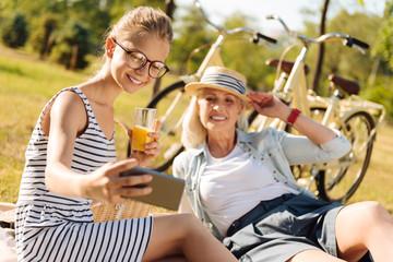 Positive grandmother and teenager girl enjoying picnic outdoors